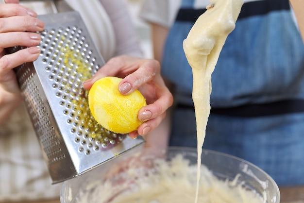 おろし金にレモンの皮をこすり、マフィンの生地を準備している女性のクローズアップ。