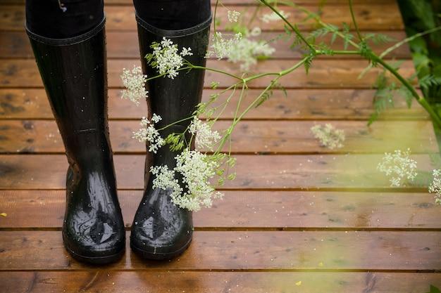 공원에서 젖은 나무 다리에 검은 고무 장화에 여자의 발의 근접 촬영. 비.