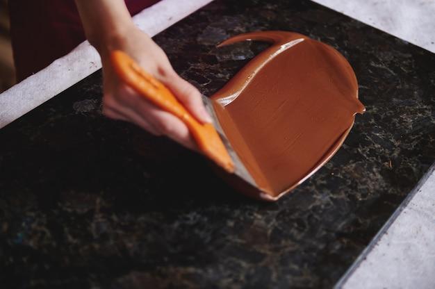 大理石の表面に溶けたチョコレートを焼き戻す女性の手のクローズアップ。ハイアングルビュー