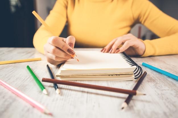 紙に書く女性の手のクローズアップ