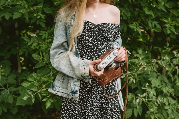 Крупным планом женские руки, держащие старую винтажную пленочную камеру