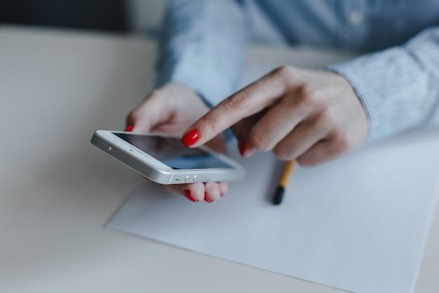 Крупным планом женские руки с красными ногтями держат и щелкают по мобильному телефону, делая платежи онлайн и болтая в синей рубашке.