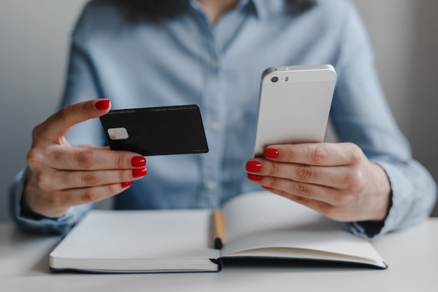Крупным планом женские руки с красными ногтями, держащие кредитную карту и мобильный сотовый телефон, делая оплату онлайн, нося синюю рубашку.
