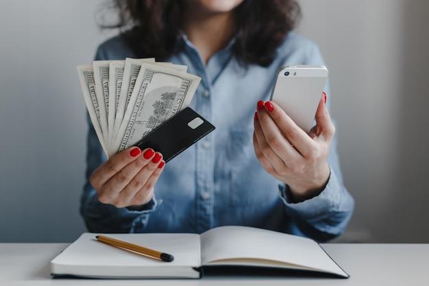 Крупным планом женские руки с красными ногтями, держащие банкноты в сто долларов, кредитную карту и телефон
