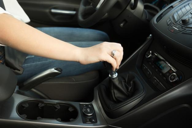 ギアスティックをシフトし、車を運転している女性のクローズアップ