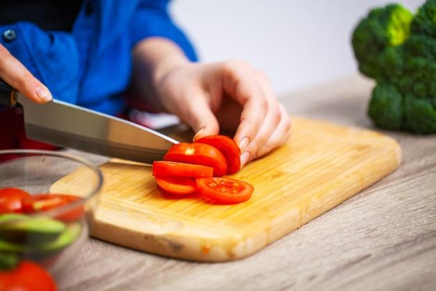 女性のクローズアップスライストマトのダイエットサラダ
