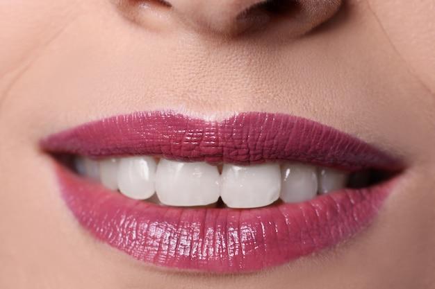 립스틱으로 칠한 부르고뉴 입술을 가진 여자 미소의 클로즈업. 전문 메이크업 컨셉