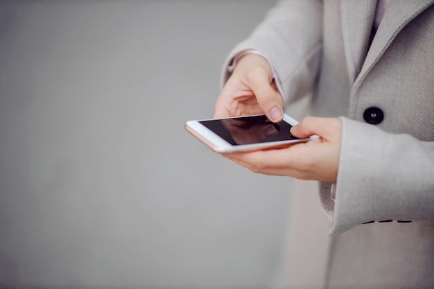 Крупным планом женщина текстовых сообщений, стоя на открытом воздухе