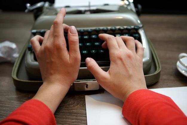 Крупным планом женщины, печатающей на старой пишущей машинке за столом