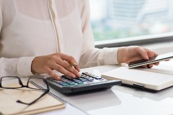 Closeup of woman using calculator and smart phone