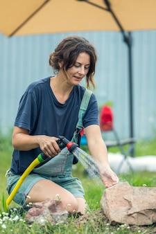 庭の植物に水をまく女性のクローズアップ
