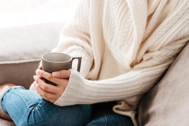 Крупным планом женщины с чашкой кофе, сидя на диване у себя дома
