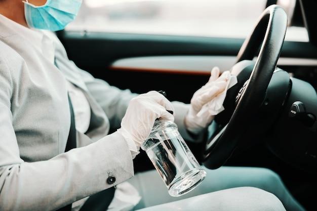 ステアリングホイールにアルコールを噴霧し、コロナウイルスの発生中に車の消毒にゴム手袋をした顔のマスクを持つ女性のクローズアップ。
