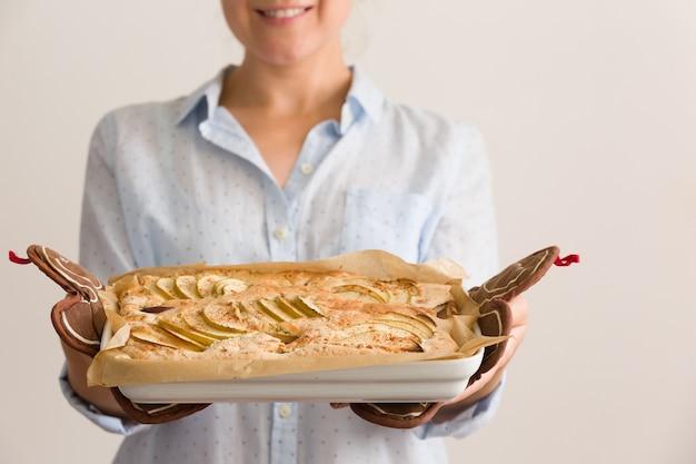 自家製クリスピーアップルパイとプレートを保持している女性の手のクローズアップ