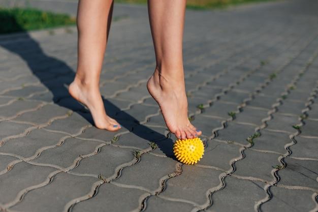 포장 석판에서 평평한 발을 쉬거나 고치기 위해 스파이크 마사지 볼에 서 있는 여성 맨발의 근접 촬영...