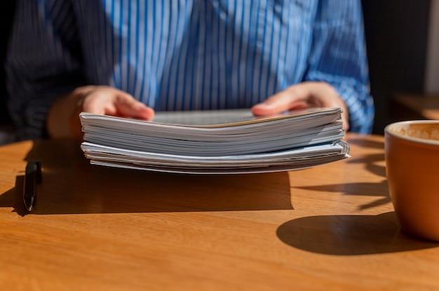 Крупным планом женские руки с кучей деловых документов над деревянным столом и чашкой кофе