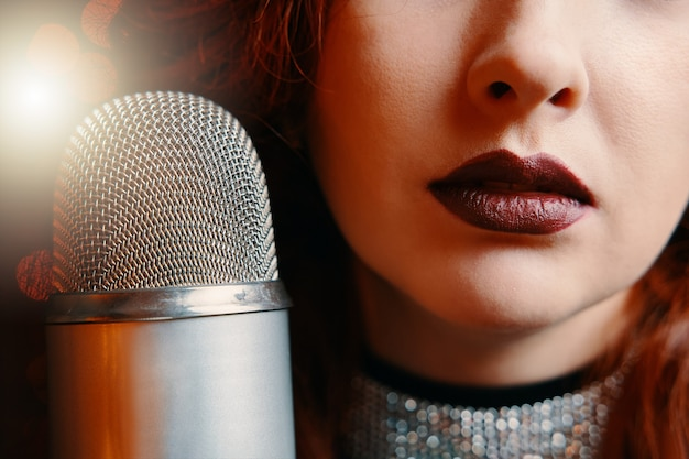 Крупным планом женские губы, накрашенные бордовой помадой, и ретро микрофон певица с дискотекой ...