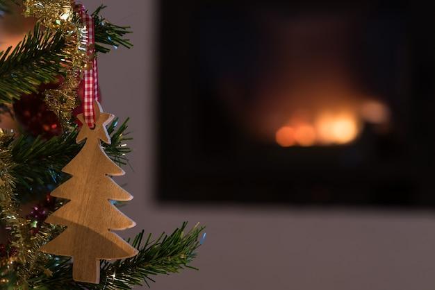 バックグラウンドで暖炉の火とクリスマスツリーにぶら下がっている木製の休日の飾りのクローズアップ。
