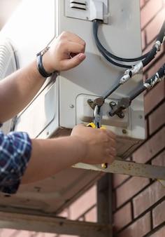 파이프를 에어컨 시스템에 연결하는 작업자의 근접 촬영