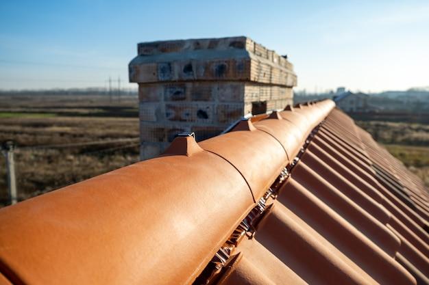 建設中の建物の屋根の上にある黄色のセラミック屋根の尾根タイルのクローズアップ。