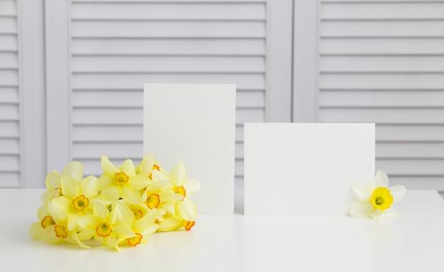 白いシャッターの上の花瓶に黄色い水仙の花のクローズアップ