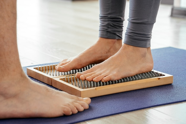 Крупным планом человека йоги, стоящего на доске садху с острыми гвоздями