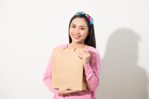 空白のクラフトパッケージを保持している若くてスタイリッシュな女の子のクローズアップ