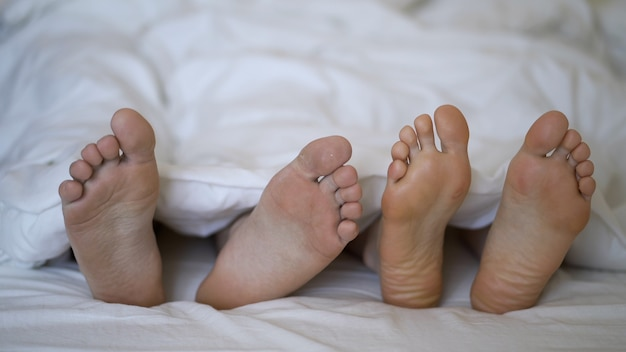 若い美しく愛情のあるカップルのクローズアップは、彼らの足を再生し、踊ります