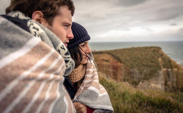 Крупным планом молодая красивая пара под одеялом в холодный день, глядя на море с темным облачным небом на заднем плане