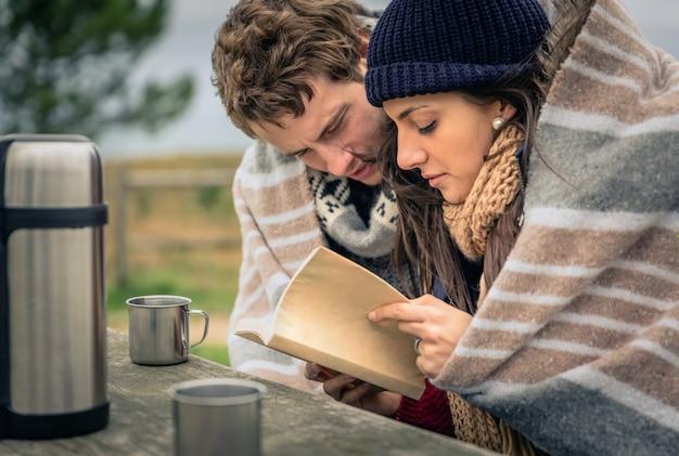 Крупным планом молодая красивая пара под одеялом, читая книгу в холодный день с морем и темным облачным небом на заднем плане