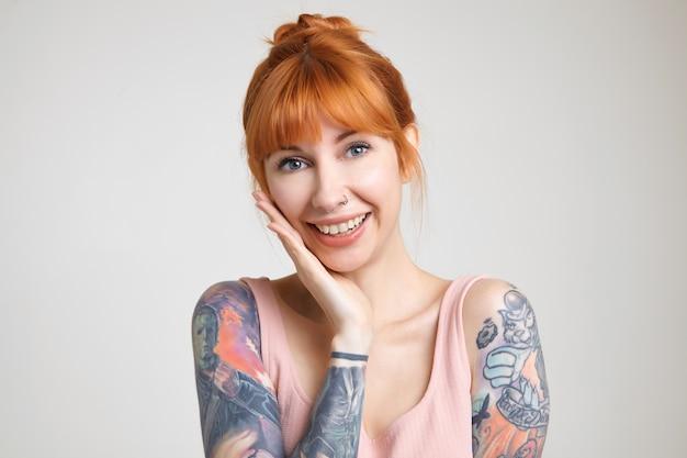上げられた手のひらに頬を傾け、白い背景の上にポーズをとっている間カメラで元気に笑っているお団子の髪型を持つ若い美しい赤毛の入れ墨の女性のクローズアップ