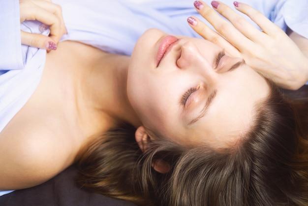 ベッドで横になっている青の若い美しい女性のクローズアップ。自然の美。 。映画のスタイル