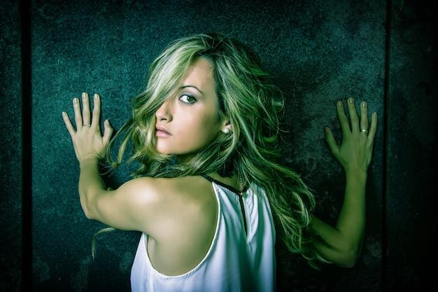 금속성 어두운 문 너머로 그녀의 손으로 겁 먹은 젊은 아름다운 여성의 근접 촬영