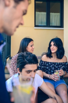 집 계단 계단에 앉아 야외에서 그녀의 여자 친구와 이야기하는 손에 레모네이드 유리와 함께 젊은 아름 다운 여자의 근접 촬영. 젊은 사람들이 라이프 스타일 개념입니다.