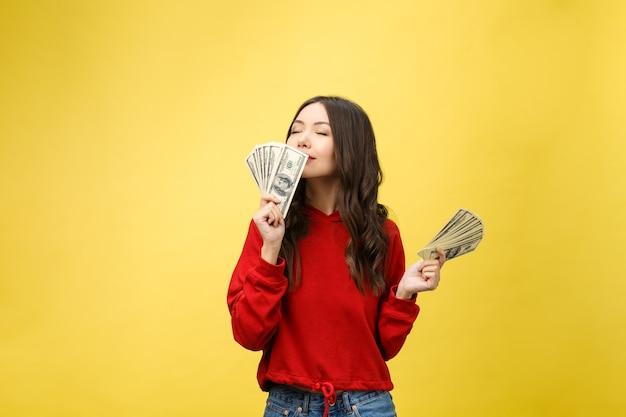 Крупным планом молодая красивая женщина с долларовыми деньгами в руке