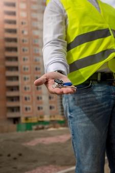 새 집에서 열쇠를 들고 젊은 건설 엔지니어의 근접 촬영