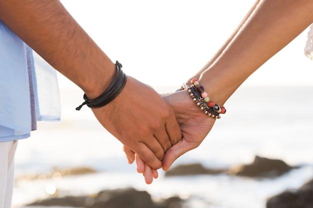 日没時にビーチで手をつないでいる若いカップルのクローズアップ