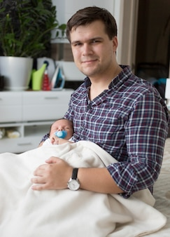 병에서 우유와 함께 귀여운 아기를 먹이 젊은 아버지의 근접 촬영