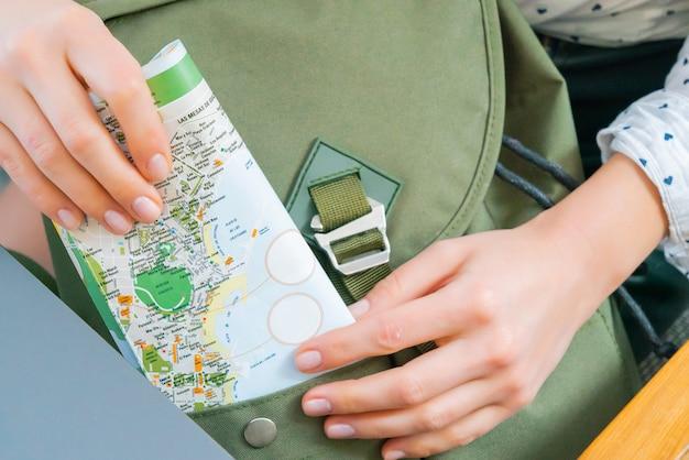 若い女の子の手のクローズアップは、バックパックに地図を置きます。旅行のための緑のヒップスターのハンドバッグ。観光コンセプト。