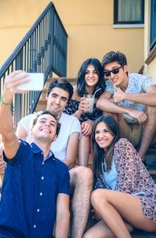 自宅の階段の階段に座っている屋外のスマートフォンで自分撮りをしている若い幸せな人々のクローズアップ。若者のライフスタイルのコンセプト。