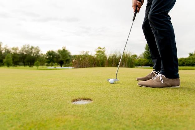 Крупным планом ноги молодого человека, играя в гольф