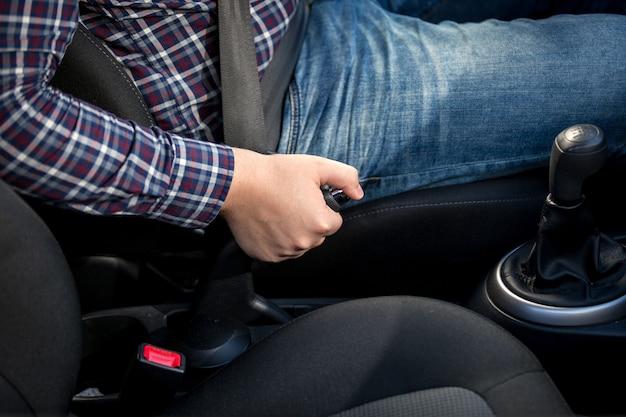 자동차에서 핸드 브레이크 레버를 당기는 젊은 남자의 근접 촬영