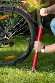 자전거 타이어를 펌핑하는 젊은 남자의 근접 촬영