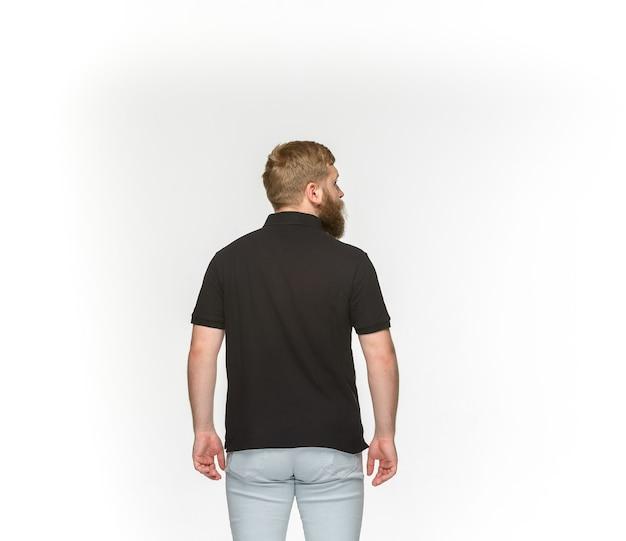 白で隔離される空の黒いtシャツで若い男の体のクローズアップ。