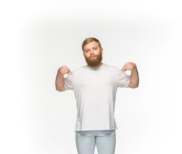 白で隔離される空の白いtシャツで若い男の体のクローズアップ。