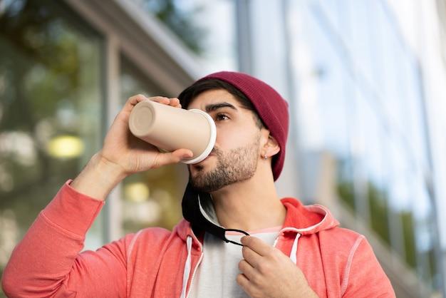 Крупным планом молодой человек в защитной маске и пить кофе, стоя на улице на улице. городская концепция. новая концепция нормального образа жизни.
