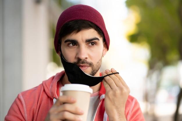 보호 마스크를 착용하고 거리에 야외에서 서있는 동안 커피를 마시는 젊은 남자의 근접 촬영