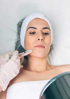 鏡で美唇治療を探している若いきれいな女性のクローズアップ。医学、ヘルスケア、美容のコンセプト。