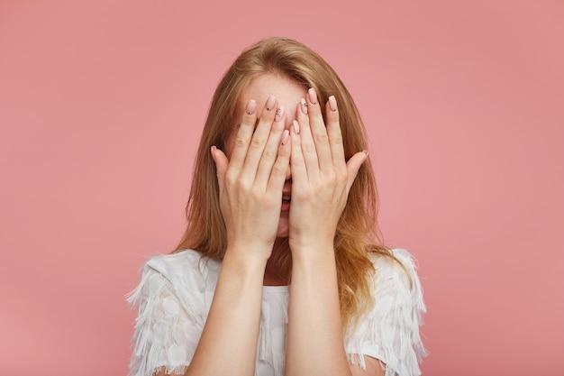 분홍색 배경 위에 포즈를 취하는 동안 흰색 우아한 티셔츠를 입고 그녀의 얼굴 앞에서 누드 매니큐어로 손을 들고 캐주얼 헤어 스타일을 유지하는 젊은 빨간 머리 여자의 근접 촬영