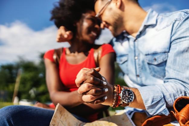 젊은 미소 다문화 힙 스터 부부의 근접 촬영 손을 잡고 아름 다운 화창한 날 야외에서 앉아